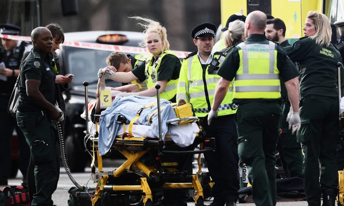 A member of the public is treated by emergency services near Westminster Bridge and the Houses of Parliament in London, England on March 22, 2017. A police officer has been stabbed near to the British Parliament and the alleged assailant shot by armed police. Scotland Yard report they have been called to an incident on Westminster Bridge where several people have been injured by a car. (Carl Court/Getty Images)