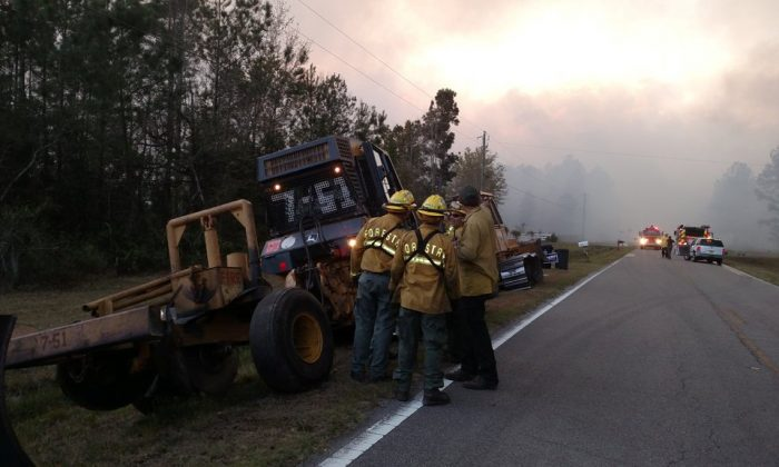 Firefighters and firefighting equipment arrive to deal with wildfire that quickly spread across acres of land, damaging many homes and forcing residents to evacuate in Nassau County, Fla., U.S. on March 22, 2017. (Courtesy Florida Forest Service/Handout via REUTERS)