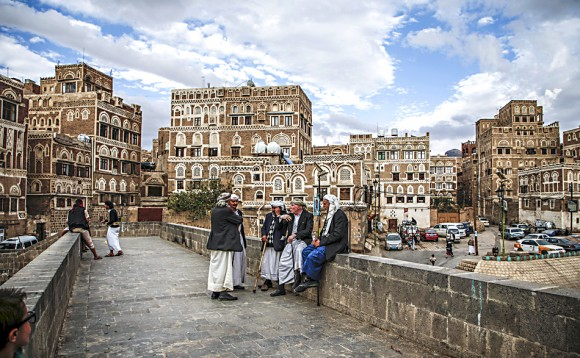Yemenis sit and talk by the ledge of a bridge with the UNESCO-listed buildings of the old city of the Yemeni capital Sanaa in background behind them, on Feb. 15, 2017. (MOHAMMED HUWAIS/AFP/Getty Images)