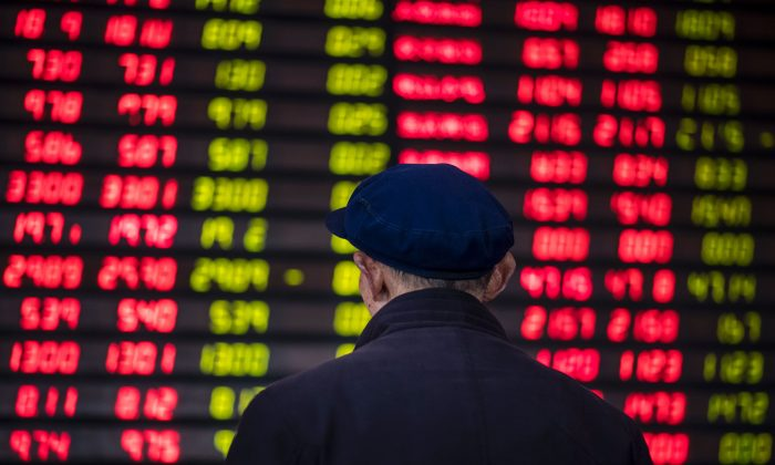 An investor looks at an electronic board showing stock information at a broker in Shanghai on March 16. (Johannes Eisele/AFP/Getty Images)
