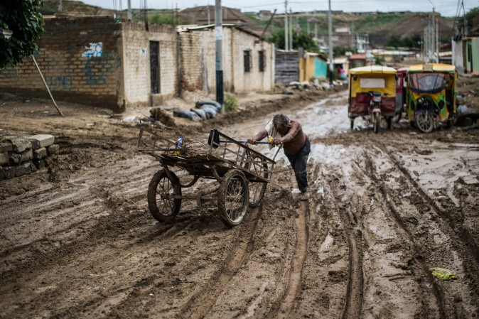 A local resident pushes his cart through the mud after flooding caused by recent rains, in the province of Paita in Piura, Peru, on March 24. The El Nino climate phenomenon is causing muddy rivers to overflow along the entire Peruvian coast, isolating communities and neighborhoods. (ERNESTO BENAVIDES/AFP/Getty Images)
