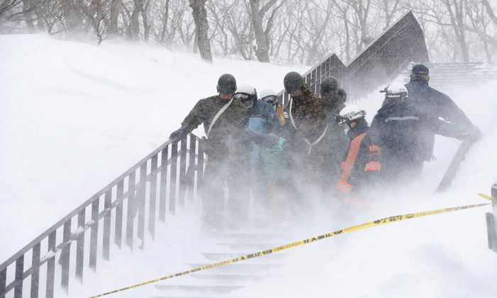 Japan Self-Defense Forces soldiers carry victims after an avalanche hit a group of high school students and teachers climbing near a ski resort in Nasu town, north of Tokyo. (Kyodo/via REUTERS)