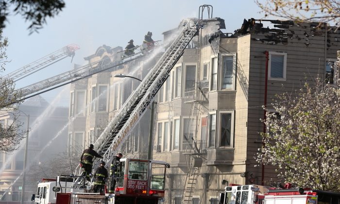 Firefighters battle a four-alarm blaze in a three-story apartment building in Oakland, Calif., on March 27, 2017. (REUTERS/Beck Diefenbach)