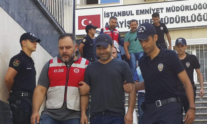 Turkish police officers escort Turkish pop singer Atilla Tas C) to the police headquarters following his arrest, in Istanbul on Sept. 3, 2016. (DHA-Depo Photos via AP)