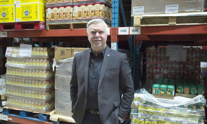 Welcome Hall Mission CEO Sam Watts stands next to pallets of food in the food bank's warehouse in Montreal on March 14, 2017. (The Canadian Press/Graham Hughes)
