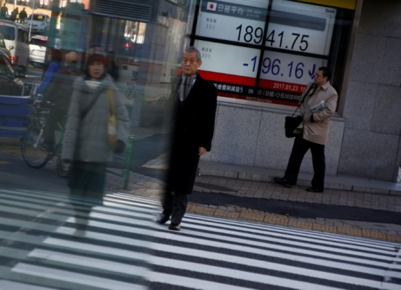 People walk past an electronic board showing stock prices outside a brokerage at a business district in Tokyo, Japan, Jan. 23, 2017.  (REUTERS/Kim Kyung-Hoon)