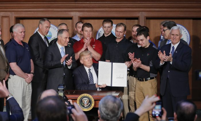 President Donald Trump, accompanied by Environmental Protection Agency (EPA) Administrator Scott Pruitt (3rd L) and Vice President Mike Pence (R) is applauded as he hold up the signed Energy Independence Executive Order at EPA headquarters in Washington on March 28, 2017. (Pablo Martinez Monsivais/AP Photo)
