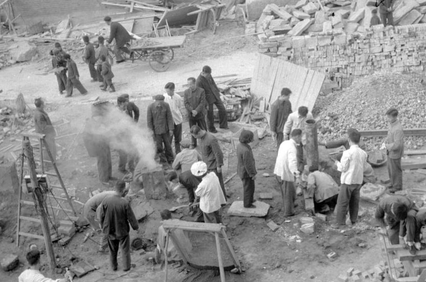 """Employees of the Shin Chiao Hotel in Beijing build in the hotel courtyard (background) a small and rudimentary smelting steel furnace during the period of the """"Great Leap Forward """" in October 1958. (JACQUET-FRANCILLON/AFP/Getty Images)"""