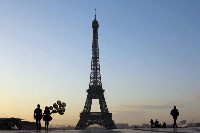 A young couple who were just recently married walk at sunrise on the Esplanade du Trocadero near the Eiffel tower in Paris on March 28. (LUDOVIC MARIN/AFP/Getty Images)