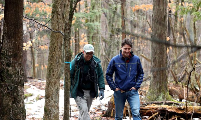 Prime Minister Justin Trudeau walks with Sheldon Lambert, Conservation manager with Parks Canada, at the Thousand Islands National Park in Gananoque, Ont., on March 28, 2017. (The Canadian Press/Lars Hagberg)