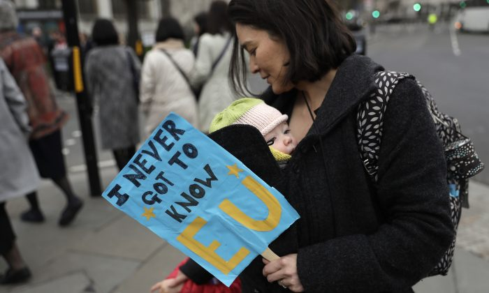 A woman carries a baby and holds a banner as she takes part in a protest outside the House of Commons in central London on March 29, 2017. (AP Photo/Matt Dunham)