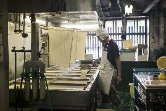 A worker making tofu at the Toyoukeya tofu shop. (Annie Wu/Epoch Times)