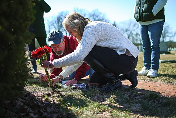 Kim Sullivan and Mark Comparone leave flowers at the grave of their son Benjamin, who died from a heroin overdose at age 27 in 2015, in Plantsville, Conn., on March 7, 2016. (John Moore/Getty Images)