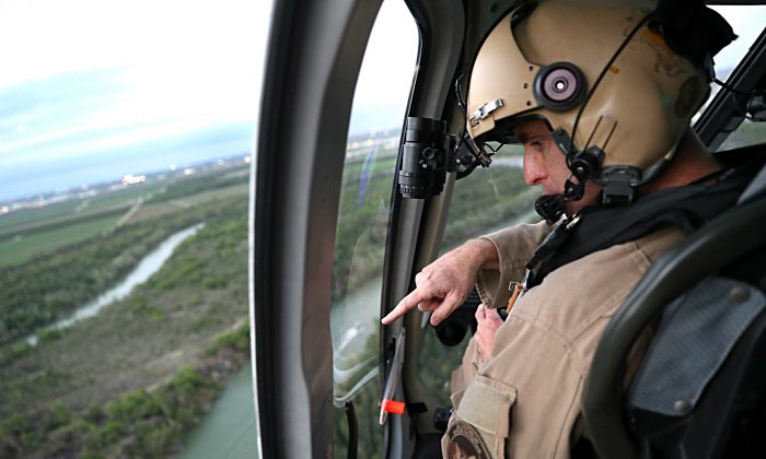 A Customs and Border Protection helicopter pilot searches for illegal immigrants while flying over the U.S.–Mexico border near La Grulla, Texas, on March 15, 2017. (John Moore/Getty Images)