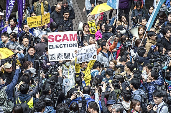 Pro-democracy activists protest outside the venue of the Hong Kong chief executive election in Hong Kong on March 26. (JAYNE RUSSELL/AFP/Getty Images)
