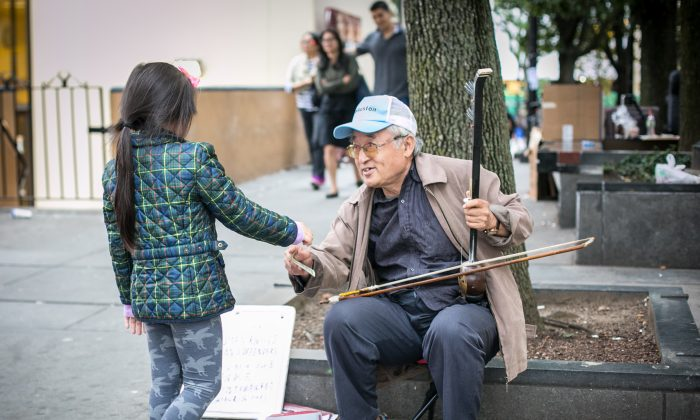 A little girl gives erhu player Xin Xiulu money in Flushing, New York, on Sept. 29, 2016.  (Benjamin Chasteen/Epoch Times)