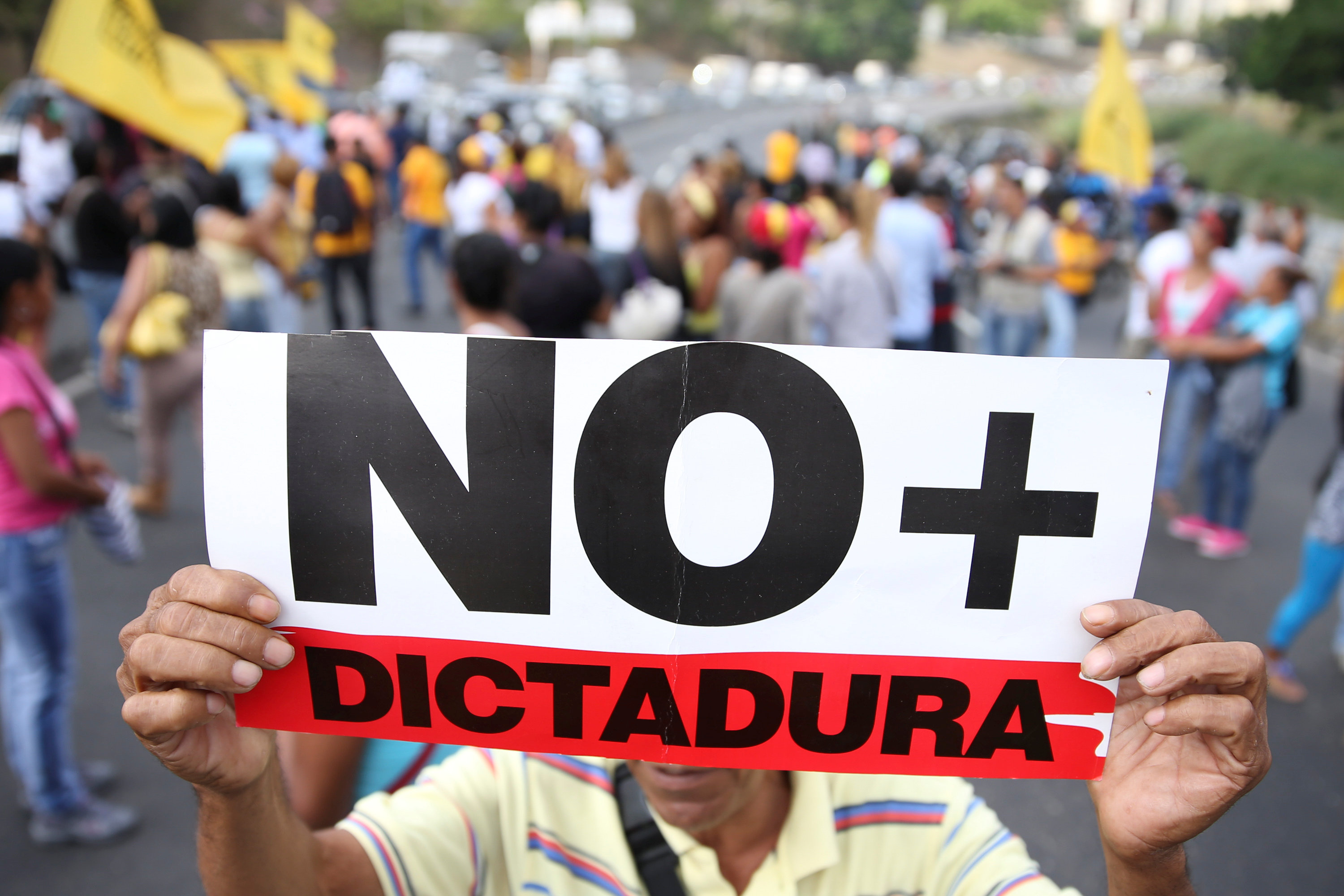 "Opposition supporters holding a placard that reads, ""No more dictatorship"" shout slogans as they block a highway during a protest against Venezuelan President Nicolas Maduro's government in Caracas, Venezuela on March 31, 2017. (REUTERS/Carlos Garcia Rawlins)"