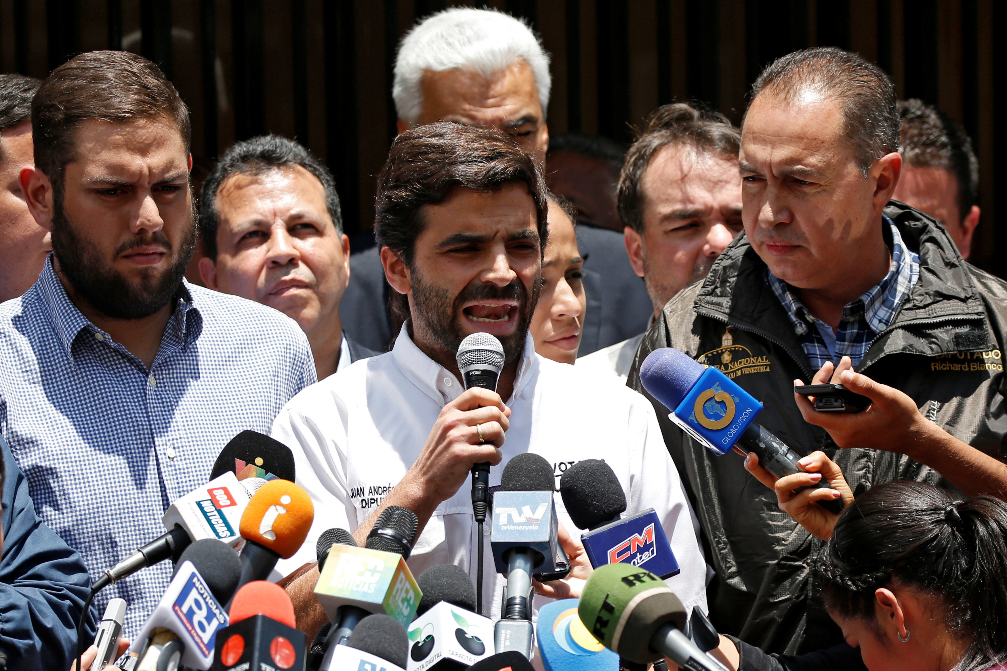 Juan Andres Mejia, deputy of Venezuelan coalition of opposition parties (MUD), talks to the media outside the offices of the opposition party Justice First (Primero Justicia), next to his fellow deputies Juan Requesens (L) and Richard Blanco (R) in Caracas, Venezuela on March 31, 2017. (REUTERS/Carlos Garcia Rawlins)