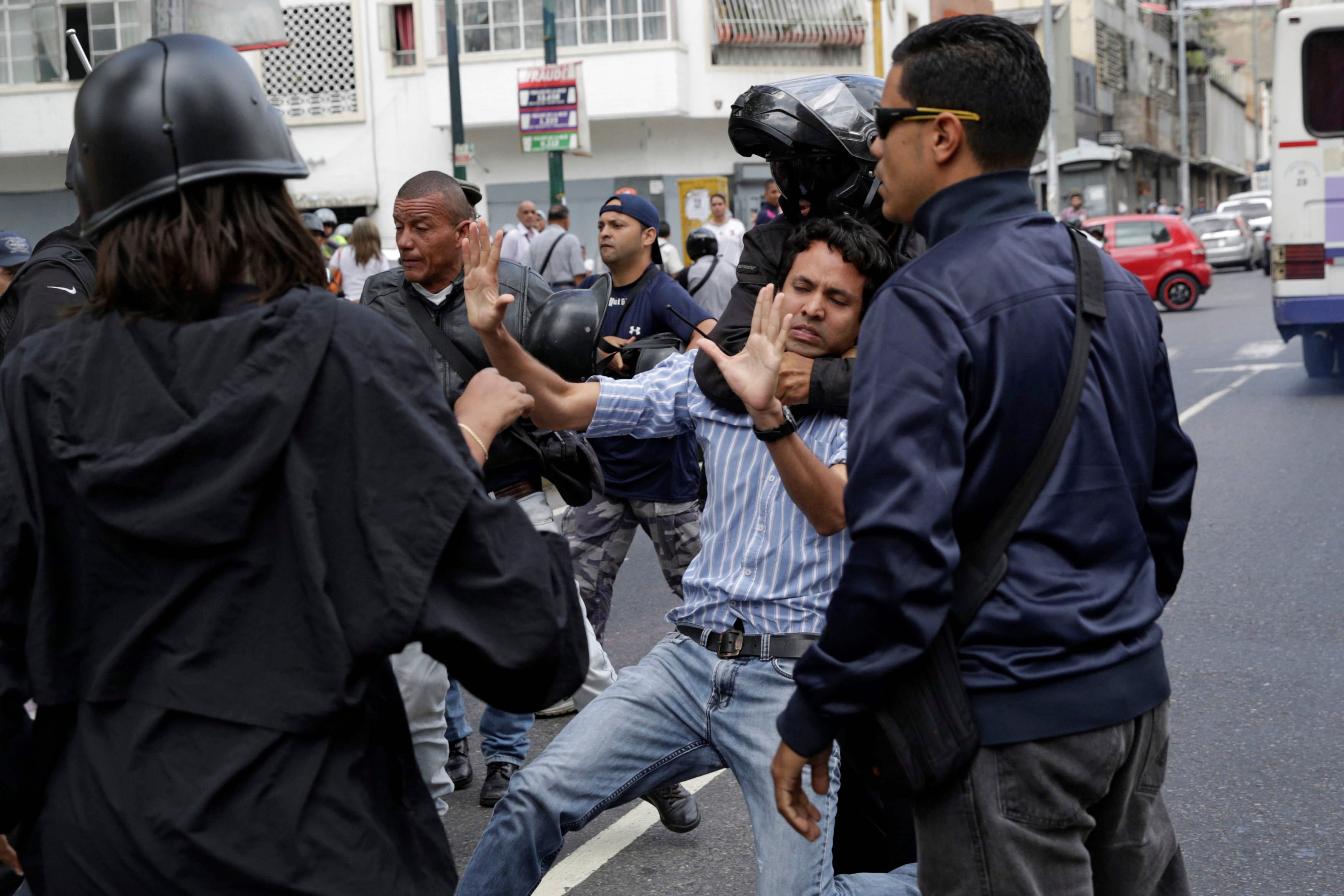 A pro-government supporter wearing a helmet grabs an opposition supporter during a protest against Venezuelan President Nicolas Maduro's government  outside the Venezuelan Prosecutor's office in Caracas, Venezuela  on March 31, 2017. (REUTERS/Marco Bello)