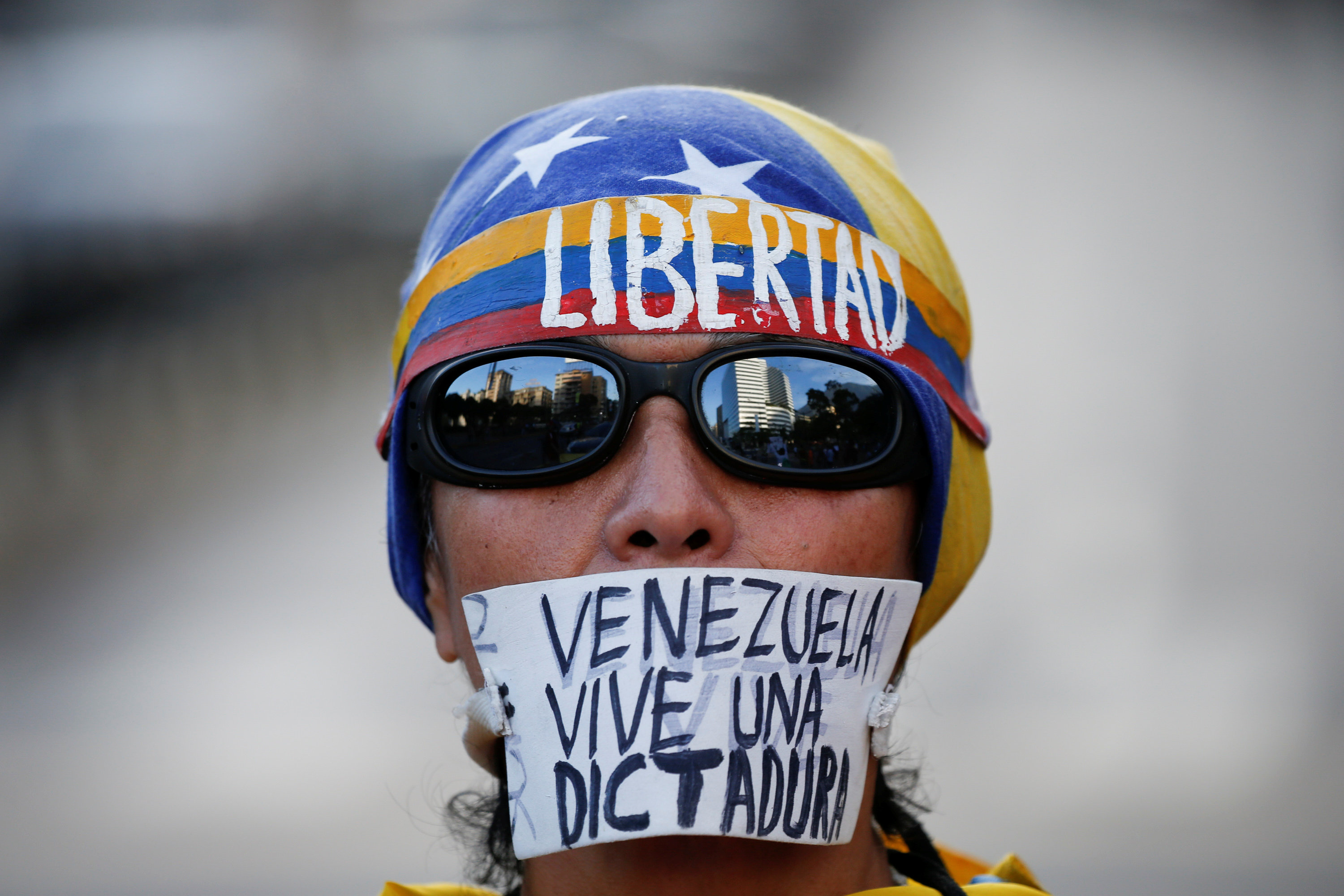 """An opposition supporter with a sign that reads, """"Venezuela lives a dictatorship"""", take part in a protest against Venezuelan President Nicolas Maduro's government in Caracas, Venezuela March 31, 2017. (REUTERS/Carlos Garcia Rawlins)"""
