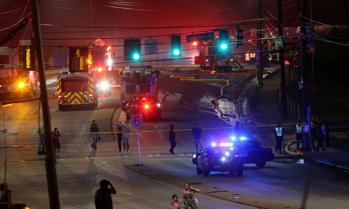 People make their way away from the bridge fire on Piedmont Road as emergency personnel work the scene of a bridge collapse at I-85 in Atlanta, Georgia. (Courtesy Curtis Compton/Atlanta Journal-Constitution/Handout via REUTERS)