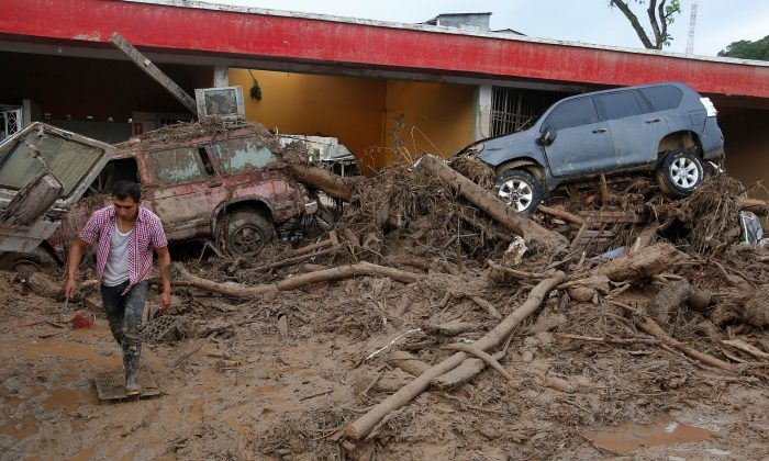 A man walks among the ruins after flooding and mudslides, caused by heavy rains leading several rivers to overflow, pushing sediment and rocks into buildings and roads, in Mocoa, Colombia April 2, 2017. (REUTERS/Jaime Saldarriaga)