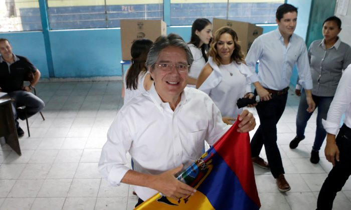 Ecuadorean presidential candidate Guillermo Lasso folds a national flag after casting his vote during the presidential election in Guayaquil, Ecuador on April 2, 2017. (REUTERS/Henry Romero)