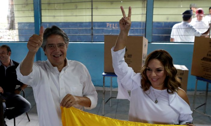 Ecuadorean presidential candidate Guillermo Lasso and his wife Maria de Lourdes Alcivar pose with an Ecuadorean flag after Lasso casted his vote during the presidential election in Guayaquil, Ecuador on April 2, 2017. (REUTERS/Henry Romero)