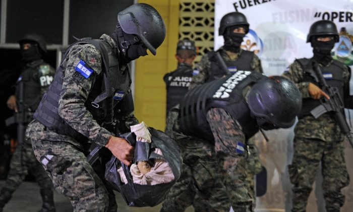 Members of the Military Police (PM) carry bags of cocaine seized to Colombian Gerson Yake Joy  (out of frame) in Tegucigalpa on Sep. 24, 2015. (ORLANDO SIERRA/AFP/Getty Images)