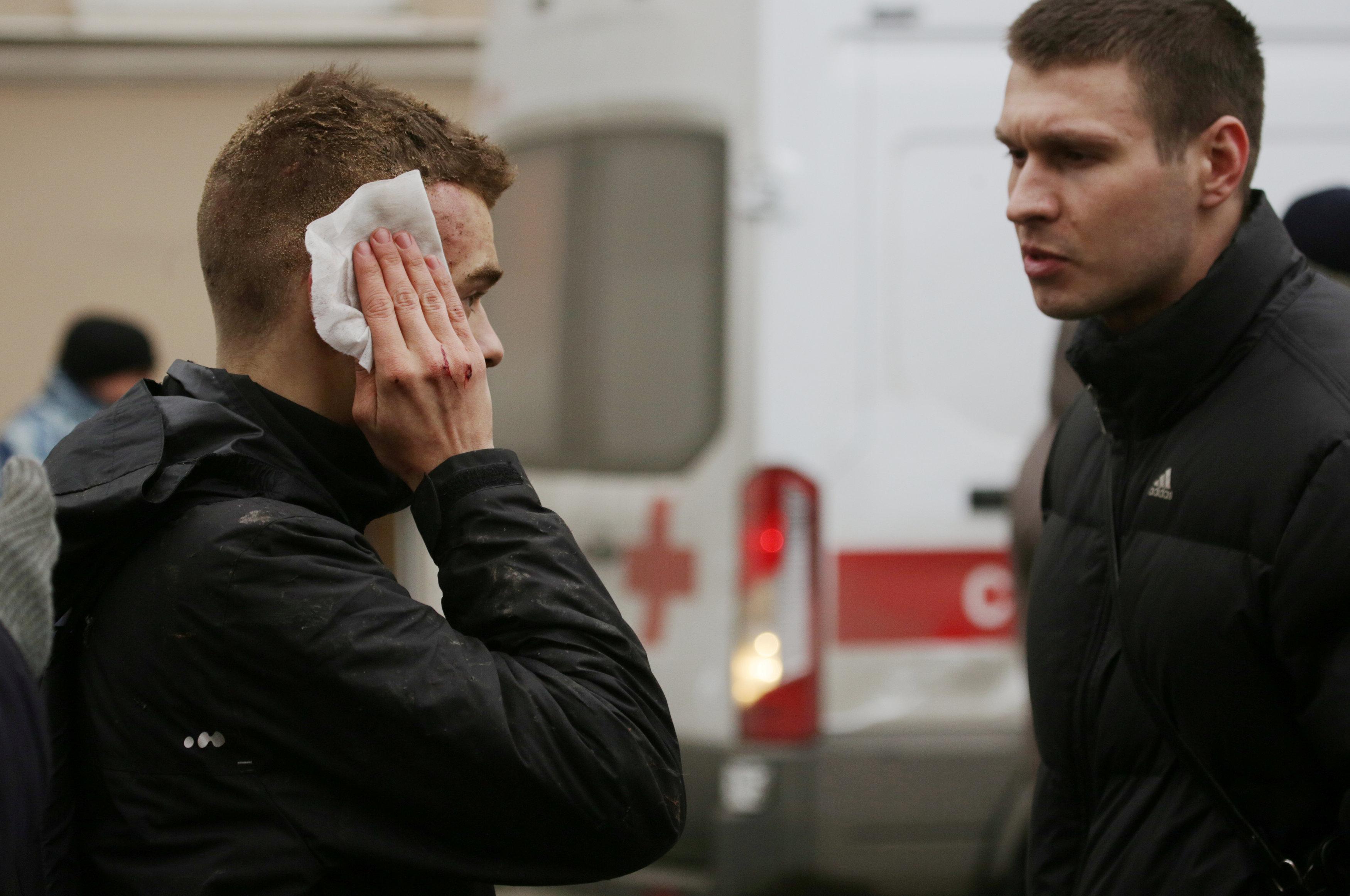 An injured person stands outside Sennaya Ploshchad metro station, following explosions in two train carriages at metro stations in St. Petersburg. (REUTERS/Anton Vaganov)