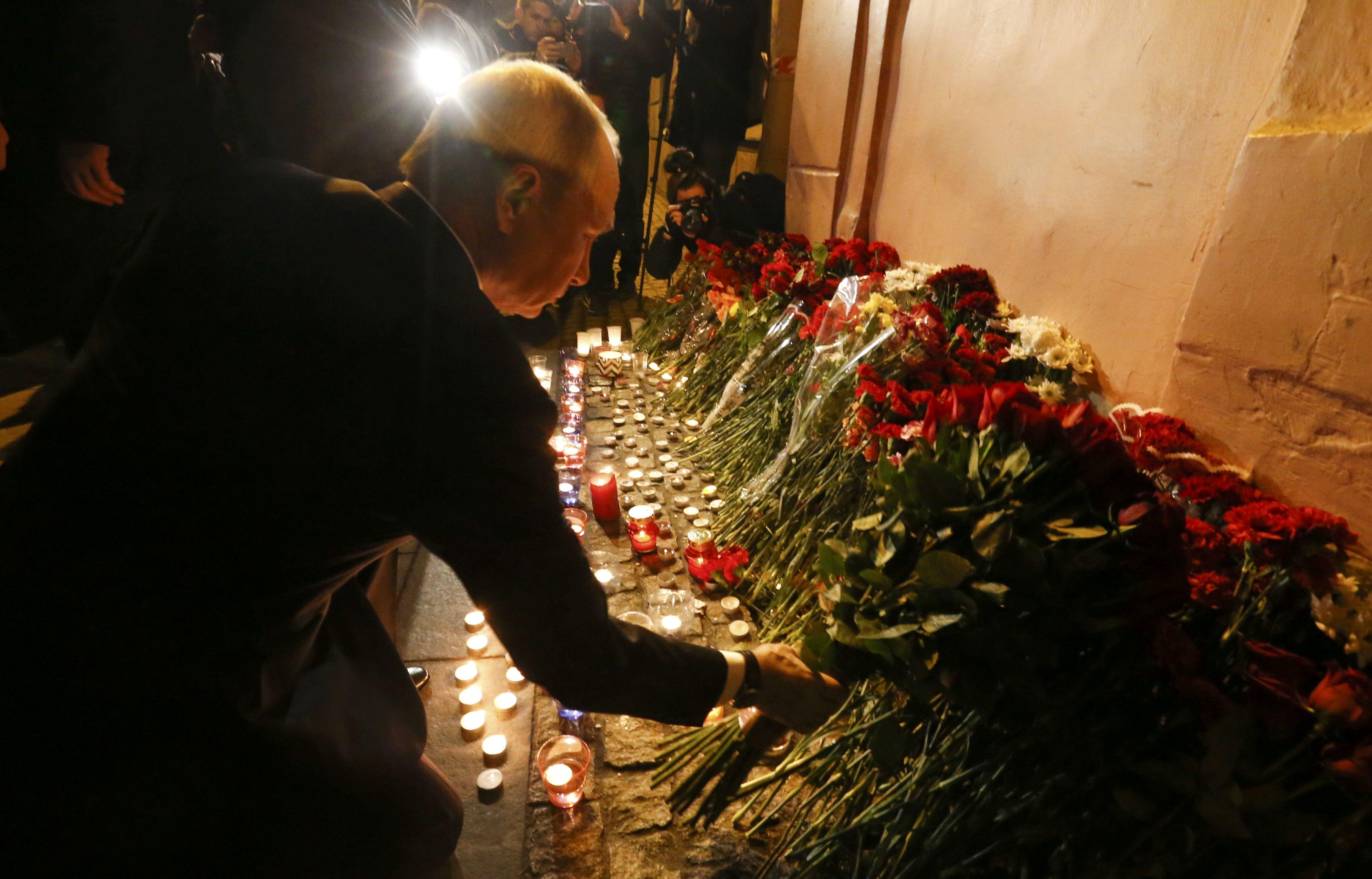 Russian president Vladimir Putin puts flowers down outside Tekhnologicheskiy Institut metro station in St. Petersburg, Russia on April 3, 2017. (REUTERS/Grigory Duko)