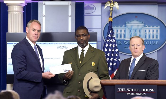 Interior Secretary Ryan Zinke, left, and Harpers Ferry National Historic Park Superintendent Tyrone Brandyburg, accompanied by White House press secretary Sean Spicer, hold up a check during the daily briefing at the White House in Washington on April 3, 2017. President Donald Trump gave his first quarter salary to the National Park Service. (AP Photo/Susan Walsh)