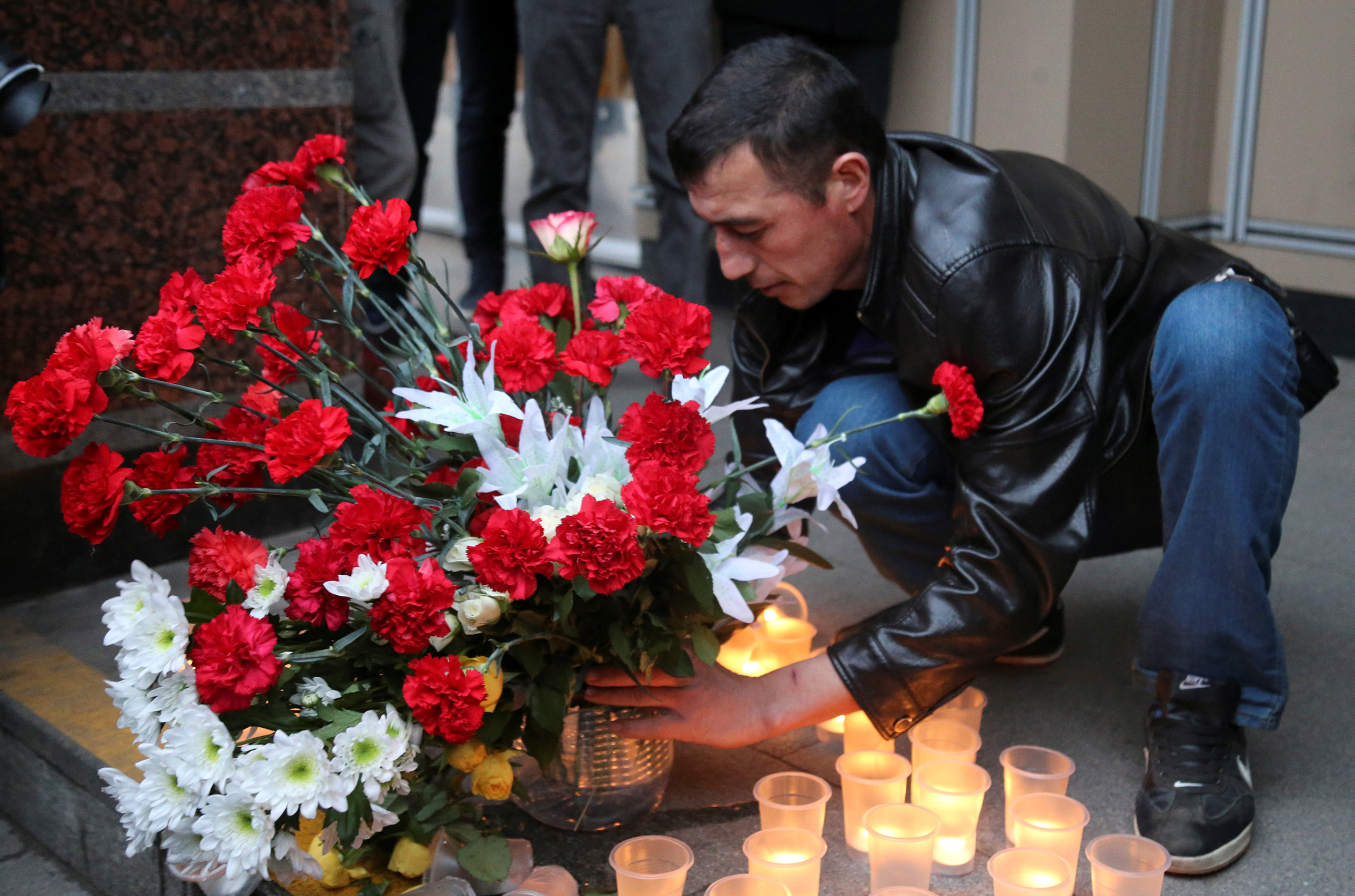 A man leaves flowers during a memorial service for victims of a blast in St.Petersburg metro, outside Sennaya Ploshchad metro station in St. Petersburg, Russia on April 3, 2017. (REUTERS/Igor Russak)