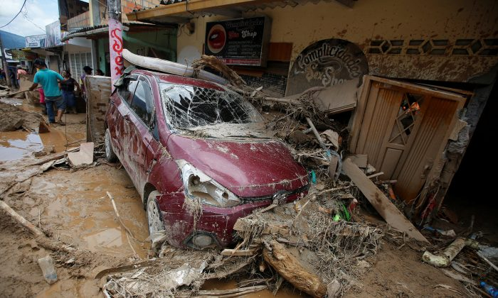 People remove debris from a destroyed street after flooding and mudslides caused by heavy rains leading several rivers to overflow, pushing sediment and rocks into buildings and roads, in Mocoa, Colombia on April 3, 2017. (REUTERS/Jaime Saldarriaga)