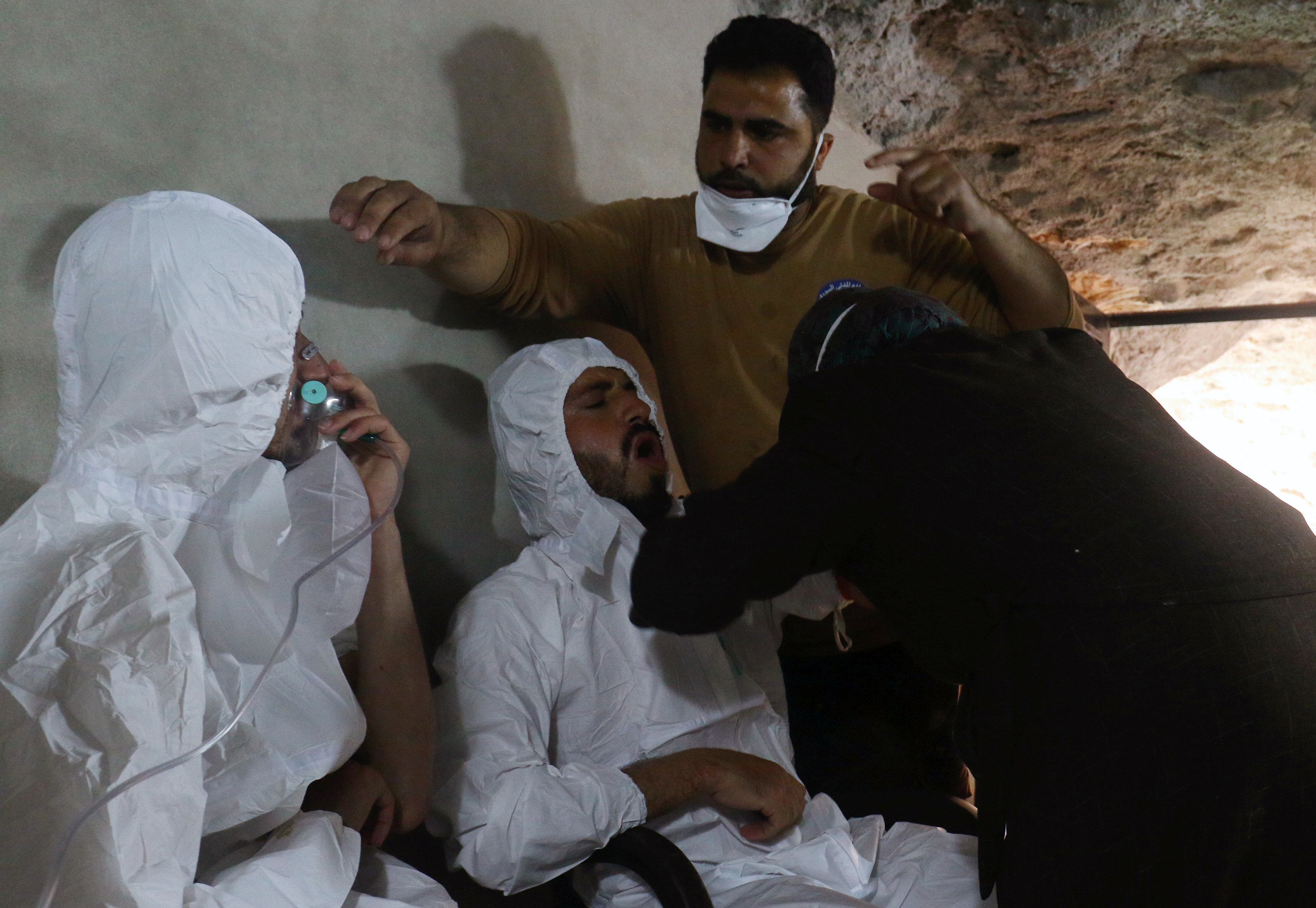 A man breathes through an oxygen mask as another one receives treatments, after what rescue workers described as a suspected gas attack in the town of Khan Sheikhoun in rebel-held Idlib, Syria on April 4, 2017. (REUTERS/Ammar Abdullah)
