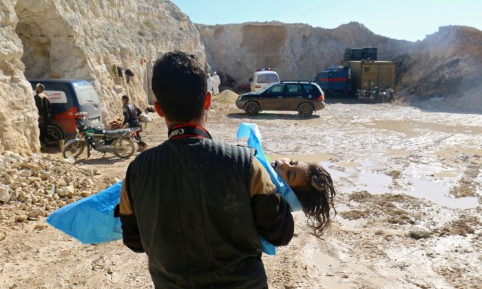 A man carries the body of a dead child, after what rescue workers described as a suspected gas attack in the town of Khan Sheikhoun in rebel-held Idlib, Syria April 4, 2017. (REUTERS/Ammar Abdullah)