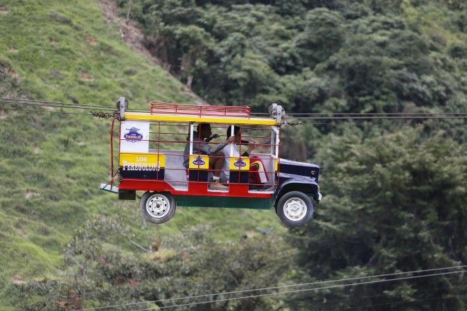 """Tourists ride a cable car in the form a of a Chiva, a bus used to serve rural routes, in Pitalito, Colombia, on April 5, 2017. The ride called """"La Chiva Voladora"""" costs about $0.70 and runs about 800 meters (875 yards) from one side of a hill to another. (AP Photo/Fernando Vergara)"""