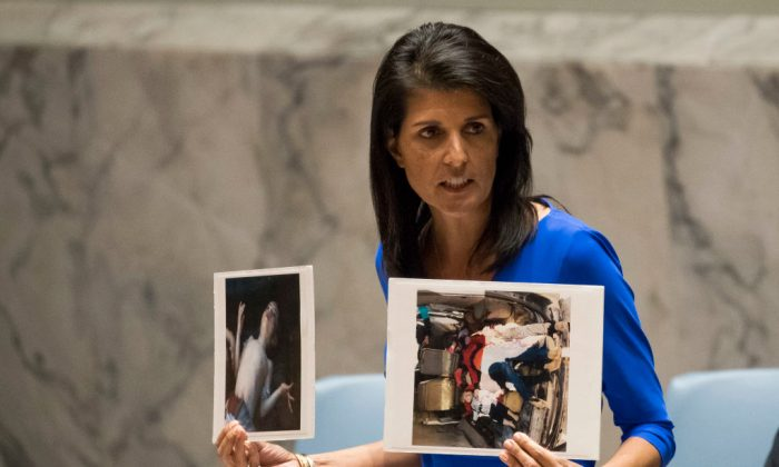 U.S. Ambassador to the United Nations Nikki Haley holds up photos of victims of the Syrian chemical attack during a meeting of the United Nations Security Council at U.N. headquarters in New York City on April 5, 2017. (Drew Angerer/Getty Images)