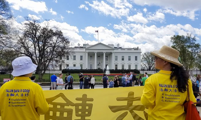Falun Gong practitioners hold a banner opposite the White House on April 4, 2017. The practitioners gathered to ask President Trump to speak to China's head of state, Xi Jinping, about ending the persecution of Falun Gong. (Bin Xue/NTD)