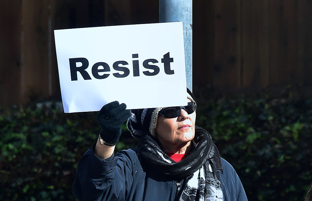 """A woman holds a placard reading """"Resist"""" as demonstrators gathered along El Camino Real in San Mateo, California on Inauguration Day on Jan. 20, 2017. (FREDERIC J. BROWN/AFP/Getty Images)"""
