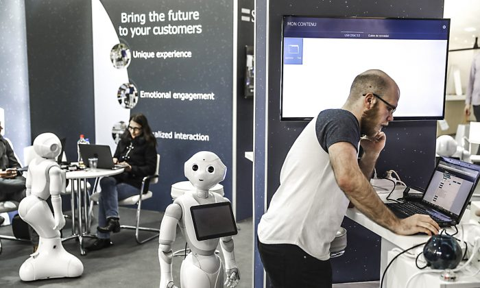 Employees and robots at the stand of SoftBank Robotics during the CeBIT fair in Hanover, Germany, on March 19, 2017. (Odd Andersen/AFP/Getty Images)