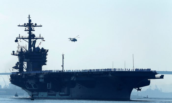 Sailors man the rails of the USS Carl Vinson, a Nimitz-class aircraft carrier, as it departs its home port in San Diego, California on Aug. 22, 2014. (REUTERS/Mike Blake/File Photo)