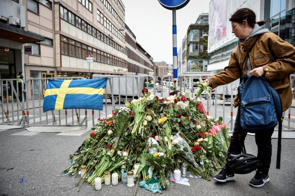 People gather at a police cordon near the crime scene in central Stockholm on April 08, 2017, the day after a hijacked beer truck plowed into pedestrians on Drottninggatan and crashed into Ahlens department store, killing four people, injuring 15 others. (TT News Agency/Noella Johansson/via REUTERS)