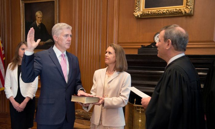Chief Justice of the United States John Roberts (R) administers the constitutional oath to judge Neil Gorsuch, as his wife Louise Gorsuch holds the bible during a private ceremony at the Supreme Court in Washington, U.S., April 10, 2017. (REUTERS/Curator's Office; Supreme Court of the United States/Handout via Reuters)