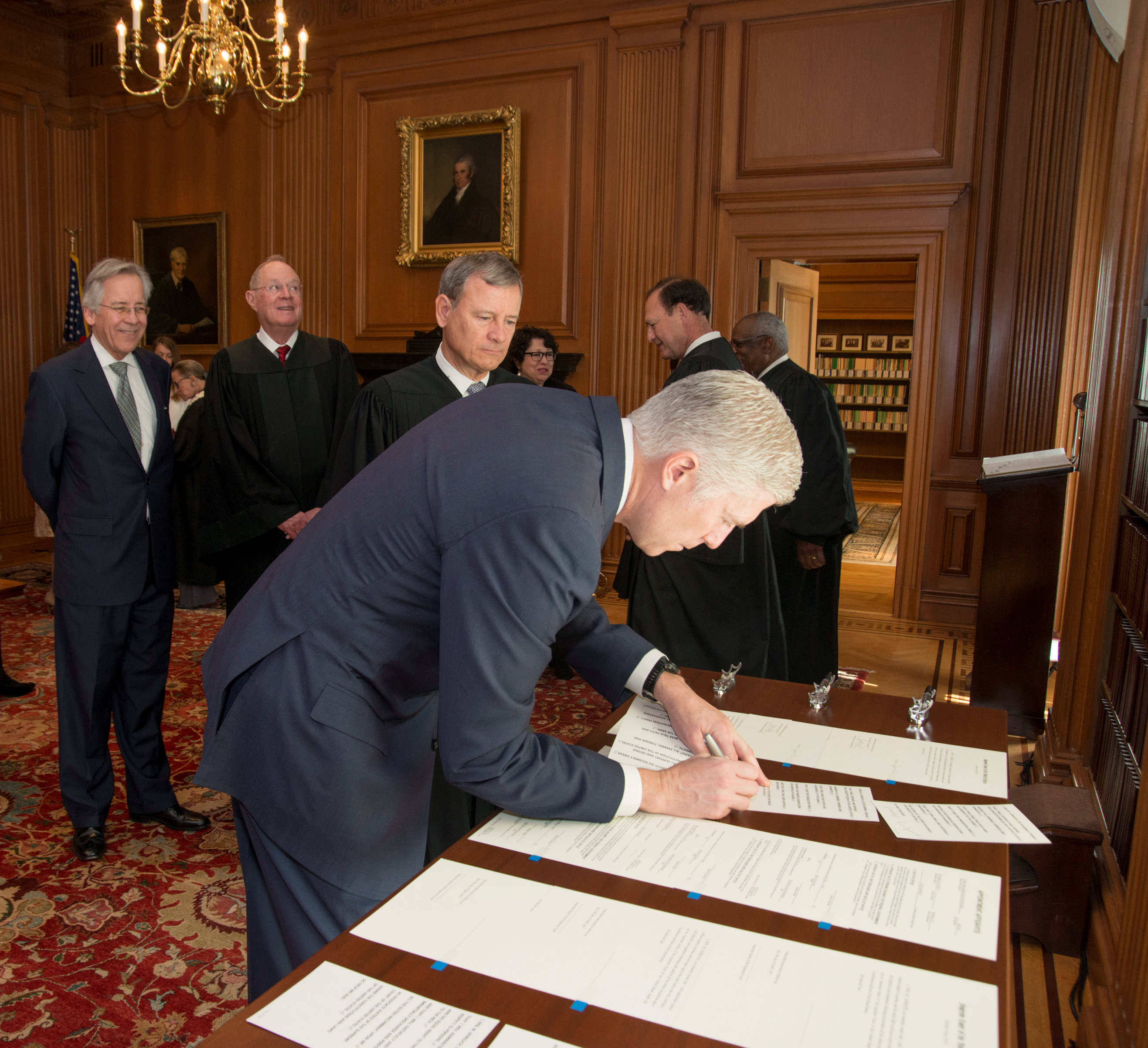 Chief Justice of the United States John Roberts (C) looks on as Judge Neil Gorsuch (R) signs the constitutional oath during swearing-in ceremony at the Supreme Court in Washington on April 10, 2017. (Courtesy Supreme Court of the United States/Handout via REUTERS)