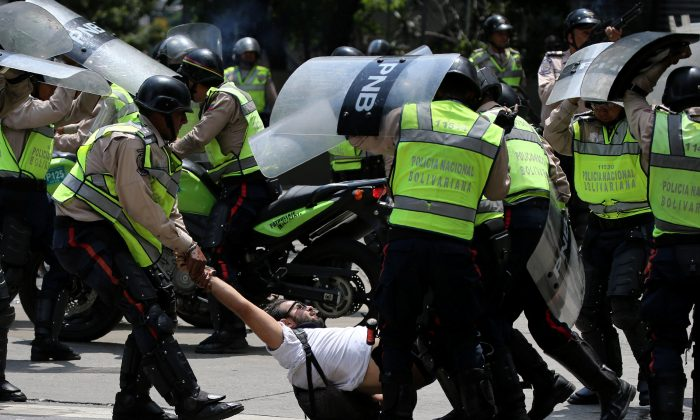 A demonstrator is arrested by riot police while rallying against Venezuela's President Nicolas Maduro's government in Caracas, Venezuela on April 10, 2017. (REUTERS/Carlos Garcia Rawlins)