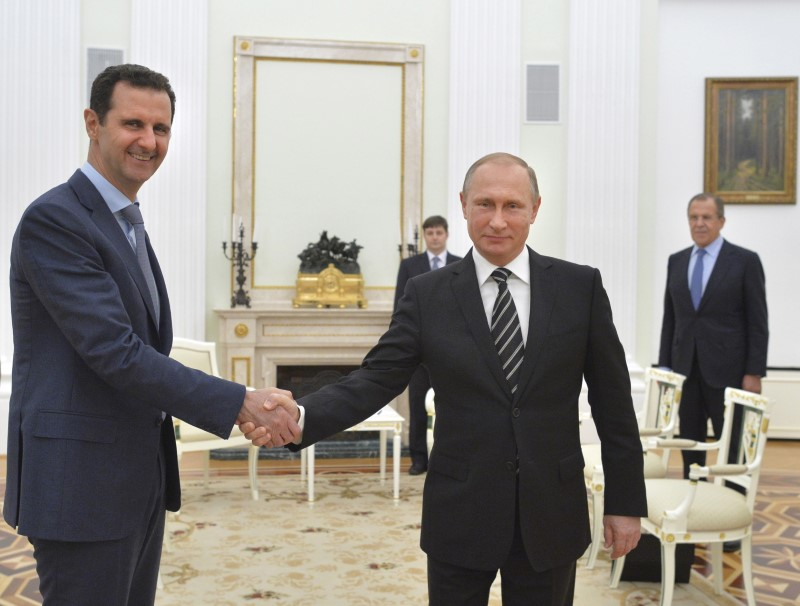 Russian President Vladimir Putin (R) shakes hands with Syrian President Bashar al-Assad during a meeting at the Kremlin in Moscow, Russia on Oct. 20, 2015. (REUTERS/Alexei Druzhinin/RIA Novosti/Kremlin)