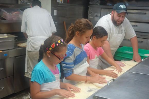 A summer enrichment program through Housing Families Inc. had staff of Pisa Pizza in Malden, Mass. teach children how to make pizza. (Housing Families, Inc.)
