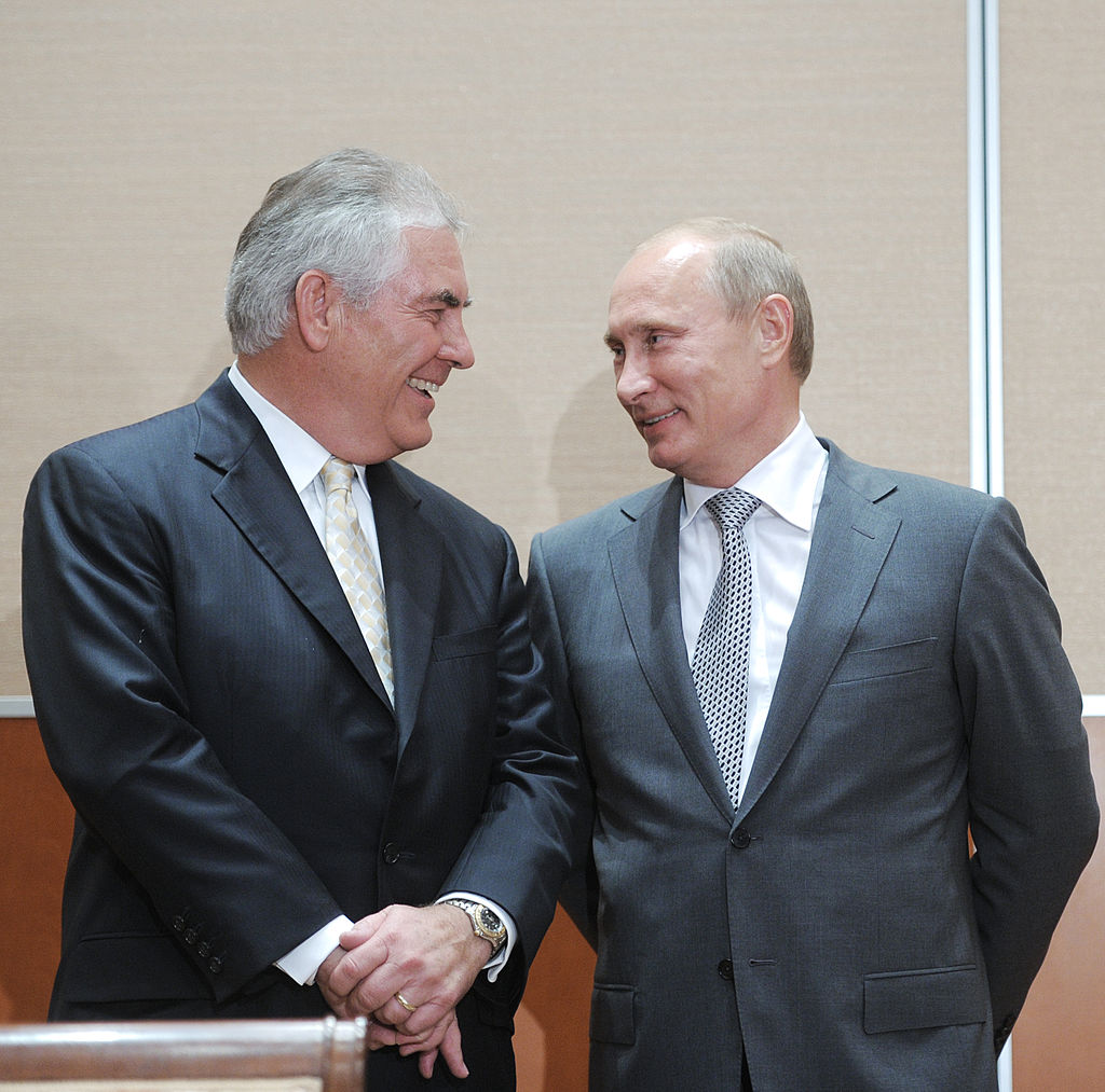 Russia's Prime Minister Vladimir Putin (L) speaks with ExxonMobil President and Chief Executive Officer Rex Tillerson during the signing of a Rosneft-ExxonMobil strategic partnership agreement in Sochi on August 30, 2011. Russia's oil champion Rosneft and US ExxonMobil clinched a global deal worth up to half-a-trillion dollars that will see the US supermajor take BP's place in pioneering Arctic exploration work.  AFP PHOTO / RIA NOVOSTI / POOL / ALEXEY DRUZHININ (Photo credit should read ALEXEY DRUZHININ/AFP/Getty Images)