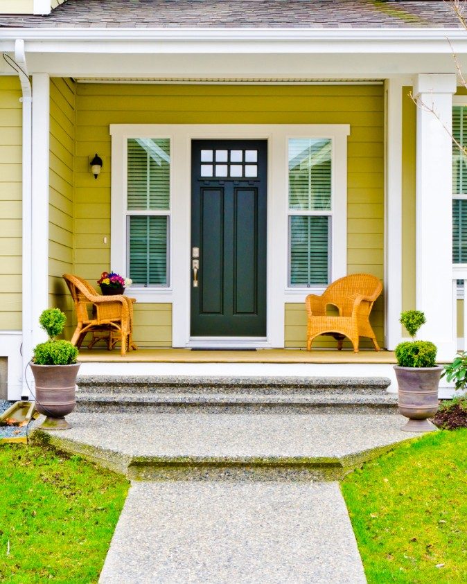 Natural wicker chairs and an ochre-painted house with white trim create a welcoming entryway. The sculptured topiaries  flanking the front door add a nice touch. (Karamysh stock photo/Shutterstock)